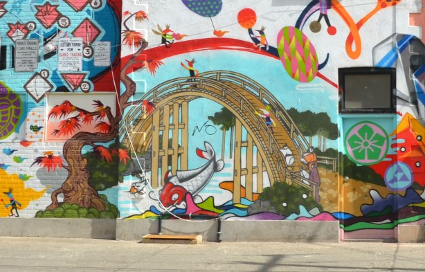 part of a mural on the side of a store on a corner lot that has a number of Japanese motifs.   Arched bridge over a stream with a fish jumping out of the water, Japanese maple tree beside the water, street art, large mural