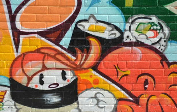 sushi street art, part of a mural on the side of a store on a corner lot that has a number of Japanese motifs.