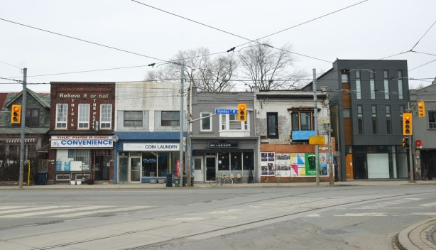 "A row of two storey brick stores on Dundas West.  A convenience store, a laundromat, a cafe, and a boarded up store.  On the exterior walls of the convenience store are the words ""Believe it or not, this is the place"""
