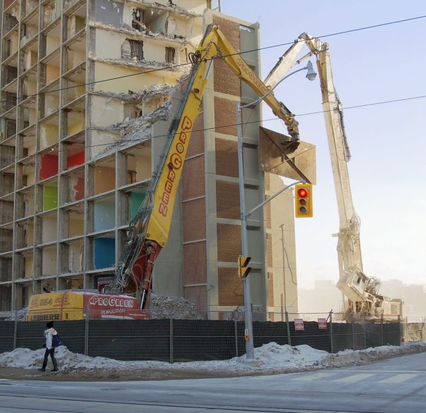 Two large cranes are demolishing an apartment building.