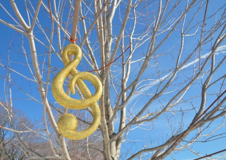 A large gold sparkly treble clef hangs from a tree branch. A decoration in winter.