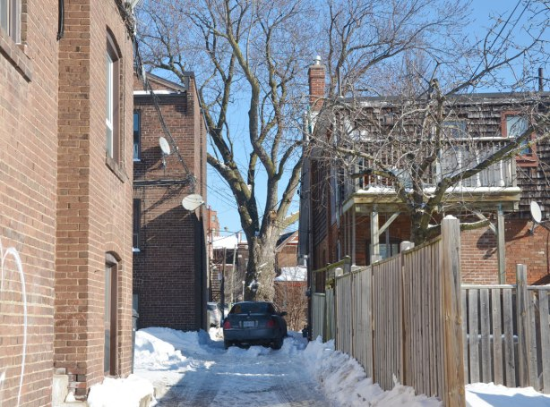 An alley with a wood fence on the right and a brick building on the left.  A car is parked at the end and just beyond the car is a large tree.  Winter time. snow.