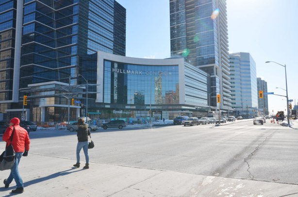 Looking diagonally across an intersection towards two tall buildings with a midsize building with a curved front in between them.