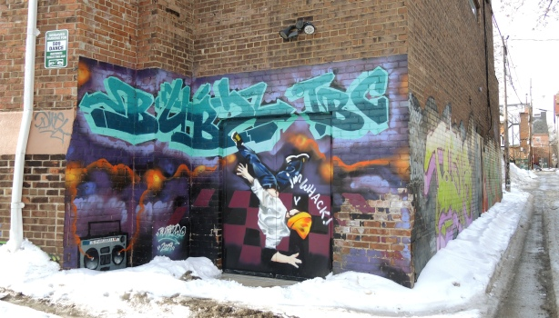 Mural over the back entrance to 509 Dance, ghetto blaster in one corner, a guy break dancing, and upside down almost, in the picture.  He's wearing a yellow hat.