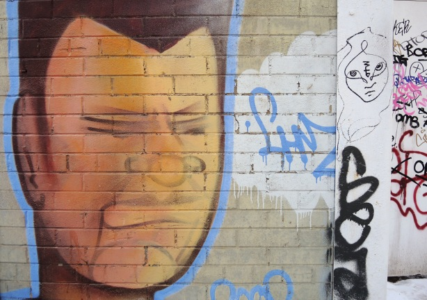 A large painted man's face on a brick wall.  Close to it is a line drawing (black on white) of a woman's face but she's much smaller.