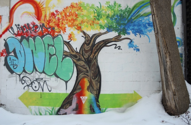 A tree with it's branches painted in rainbow colours, from left to right: red, orange, yellow, green, blue.  A man is sitting at the base of the tree, back to the viewer, in a yoga position.  Unfortunately, part of the mural has been tagged over in sea foam green DWEL.  Wintertime, snow on the ground.