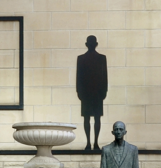 Close up of a bronze sculpture of a man.  In this picture you can only see his head and shoulders.  Behind him on a wall is a black silhouette that looks like his shadow.  A large white planter is also in the picture although there is nothing growing in it.