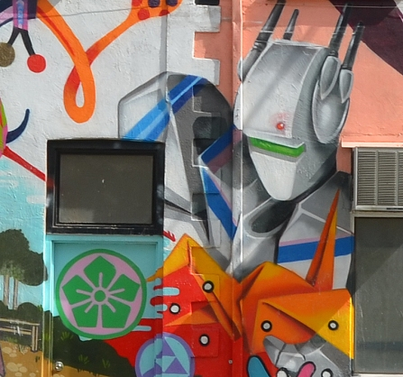 Street art, part of Japanese-Canadian mural, of a robot looking down at the door.
