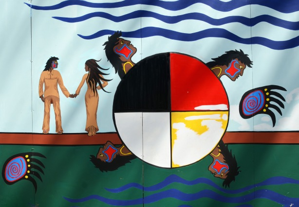 part of an Anishnawbe First Nations story/legend themed mural painted on wood construction hoardings in Allan Gardens - a couple walking hand in hand beside a circle divided into quarters, one is black and one is red and a head comes out of each quadrant.
