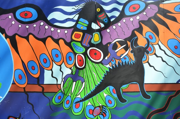 part of an Anishnawbe First Nations story/legend themed mural painted on wood construction hoardings in Allan Gardens - a stylized eagle in bright colours in flight.