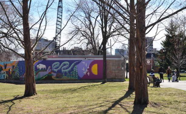 part of a First Nations story/legend themed mural painted on wood construction hoardings in Allan Gardens seen from back a bit, tees, construction equipment and a couple of people are also in the picture