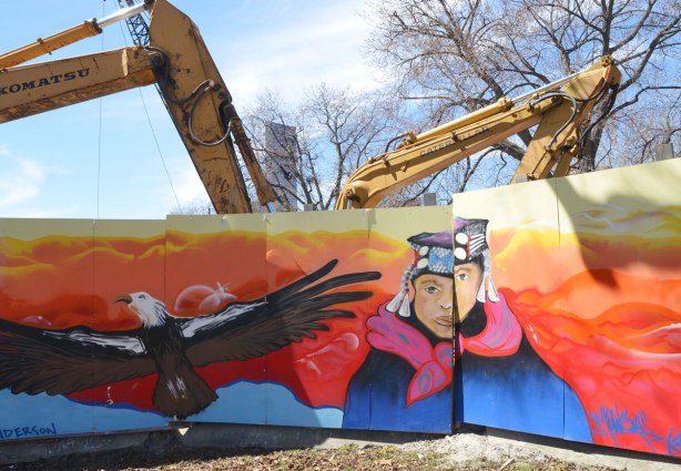 part of First Nations story/legend themed mural painted on wood construction hoardings in Allan Gardens, a eagle in flight and a man.  construction equipment can be seen bei=hind