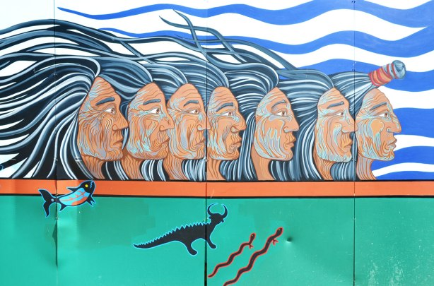 part of a First Nations story/legend themed mural painted on wood construction hoardings in Allan Gardens - a row of 6 men's heads seen in profile, all looking to the right, their long hair blowing away from their faces.