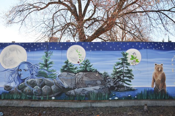 part of a First Nations story/legend themed mural painted on wood construction hoardings in Allan Gardens a leafless tree and a couple of smaller pines by a lake