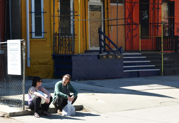 A couple is sitting on the sidealk outside a row of boarded up houses.  The houses are brick and are painted in bright yellow, orange and red.