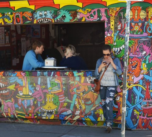 A couple is sitting by a window inside a restaurant.  The exterior wall of the building is covered in a mural of brightly coloured little monsters.  A woman is standing outside by the window as she checks her phone.
