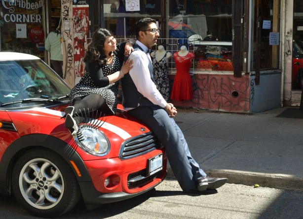A couple is posing for engagement photos.  She is sitting on the hood of a red and white Mini Cooper.  He is leaning against the front of the car.  The car has big eyelashes over the front headlights.  The car is parked on a street in Kensington.
