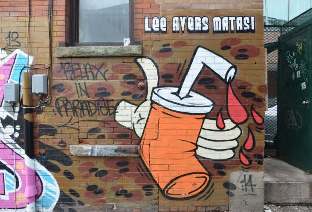 "Picture of an orange pop can being crushed by a white hand.  There are drops of red liquid (blood?) coming out of the straw that is in the top of the can.  The words ""Lee Avers Matasi"" are written in block letters above the picture."