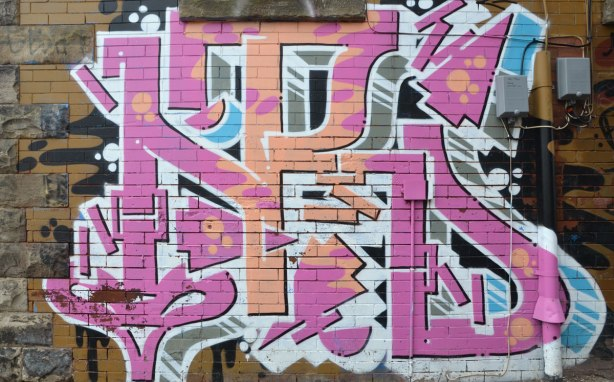 pink and pale orange graffiti tag painted on a brick wall in a Toronto alley