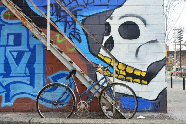 large white skull with yellow teeth, and mouth partially open painted on a wall by a metal exterior staircase.  The skull is talking black symbols all jumbled up in a blue speech bubble.  There is a bike parked in front of the stairs.  Perhaps the skull is about to eat the bike?