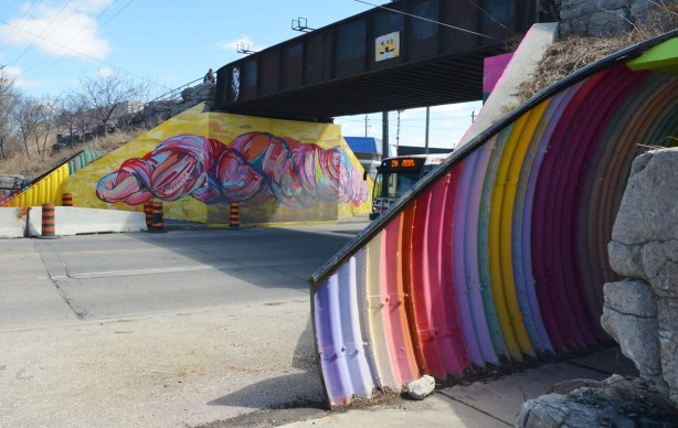 A Dufferin street TTC bus passes under an old railway bridge.  The concrete support on the far side has been painted with a brightly coloured skein of wool on a yellow background.  In the foreground is a culvert that is used as a bridge over a sidewalk.  It has been painted in bright vertical stripes.