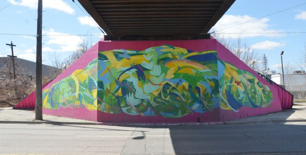 Mural of a skein of wool in bright colours on the underpass of a bridge