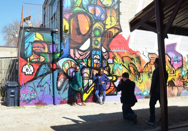 Two women are posing in front of a mural in a Kensington lane while a man takes a picture and another man watches.