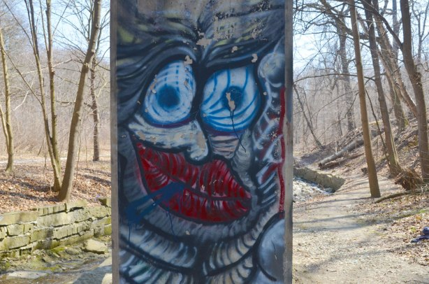 Graffiti faces on concrete pillars supporting a bridge - wild blue eyes and red lips with wavy skin, with the trees, creek and path through the ravine in the background.