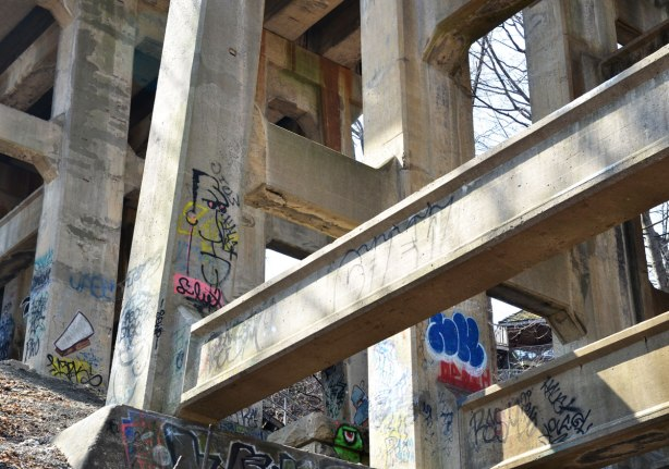 Graffiti faces on concrete pillars supporting a bridge - looking up from below so there are a large number of supports visible.  A line drawing of a man's head is on one of the pillars