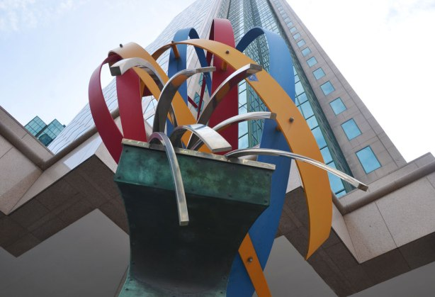 Looking up from underneath a sculpture, Public art on a corner called 'The Wave' by Ivan Kostov. curved pieces of coloured metal on top of a greenish pedestal. A highrise condo building is behind.