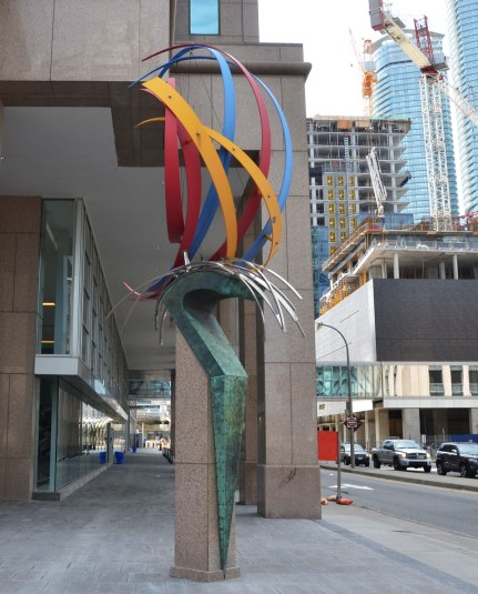 Public art on a corner called 'The Wave' by Ivan Kostov. curved pieces of coloured metal on top of a greenish pedestal.