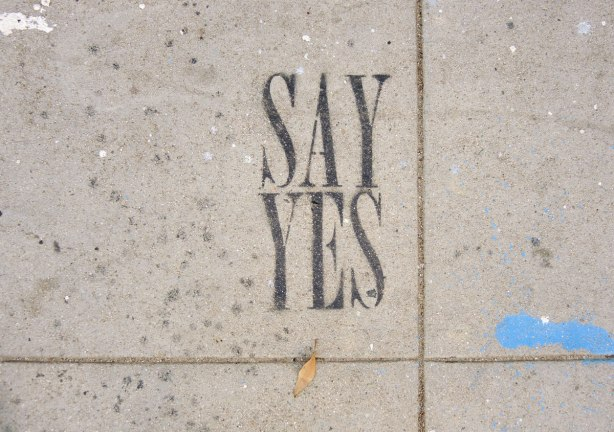 "black paint with stencil graffiti on a sidewalk - large block letters that say ""say yes'"