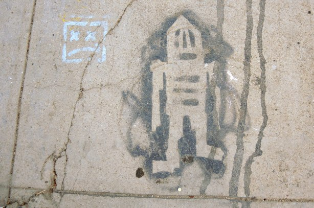 black paint with stencil graffiti on a sidewalk - stickman (or maybe stikman)