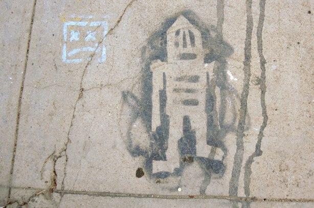black paint with stencil graffiti on a sidewalk - stickman (or maybe stikman)