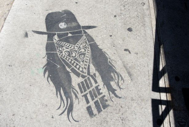 black paint with stencil graffiti on a sidewalk - person with long hair, a cowboy hat, sunglasses and a bandana covering face from nose down.