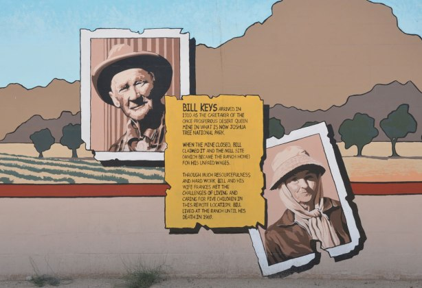 part of a mural showing a portrait of Bill Keys (as an old photograph) and his wife.  In the middle of the painting is text that tells the story of their ranch in 29 palms.