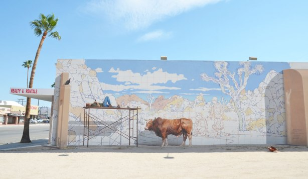 mural of a man lying on his back on scaffolding.  He is painting a mural that is unfinished.  The sky is blue.  Other parts are drawn and labelled as to which color they should be painted.  A very realistic cow stands beside the scaffolding.