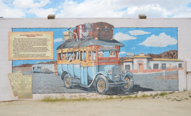 a mural that illustrates the story of the 29 Palms stage and express.  An old truck is full of people and there are trunks and bags tied to its roof.