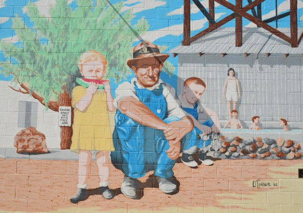 mural, a young girl is eating a slice of watermelon while a man in blue overalls is sitting beside her.  Other children are in the background.