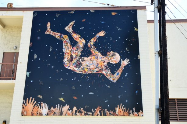 A large mural on the side of a building in La Jolla, a man is falling towards a lot of uplifted hands.  The man is painted with a number of jumbled up body parts.