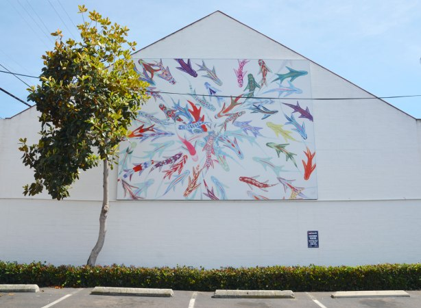 A large mural on the side of a white building.  Many fish in many colours are swimming around on a white background.   A small tree partially blocks the left side of the mural.