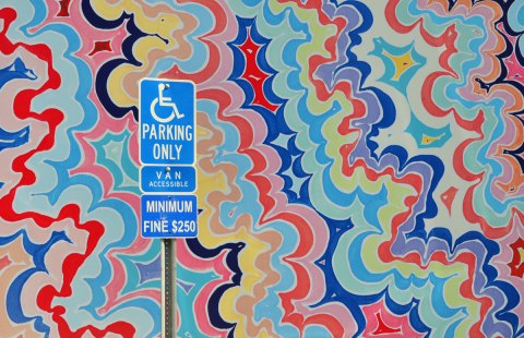 Close up of a large mural of concentric circles of wavy lines, almost psychadelic  in nature.   A blue and white handicap parking spot sign is in front of it.