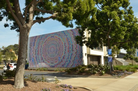 a large mural of concentric circles of wavy lines, almost psychadelic  in nature on the side of a building that is partially obscured by a tree.