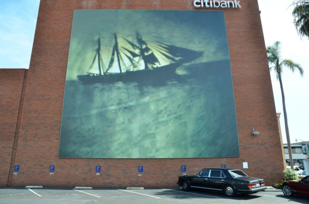 A very large mural in shades of greenish blacks and greys of a sailing ship at sea.