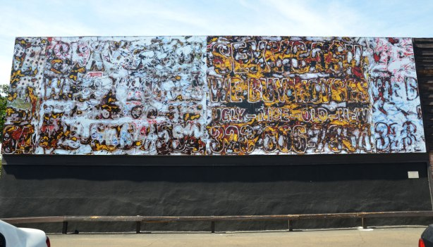 A long horizontal mural on the side of a building.  Messy looking but there are a few large numbers and letters visible.
