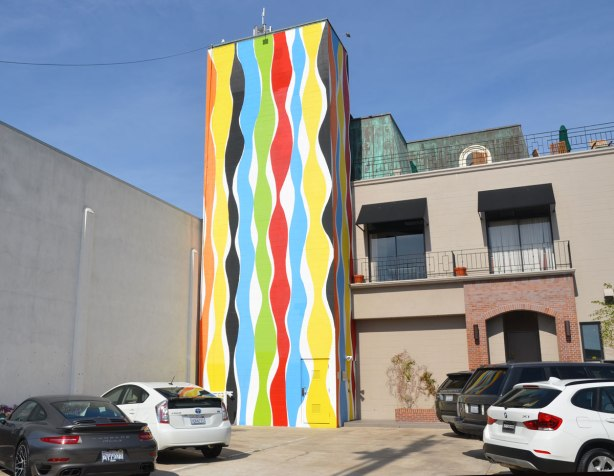 Tall vertical mural of wavy stripes of colour on white background.  Red, blue, yellow, green and black stripes.  More than 2 storeys tall.