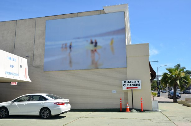 A large mural of a beach scene in washed out colours, soft focus, on the side of a building beside the parking lot in front of Quality Cleaners in La Jolla.
