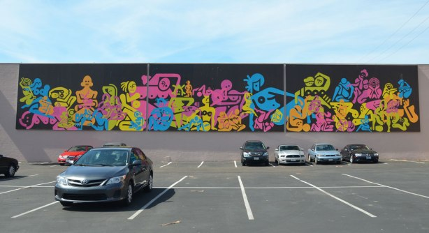A few cars parked in a parking lot that has a very long mural titled 53 women because there are 53 women in the mural...  black background and abstract silhouettes of women in bright colours.  All naked, all women are one colour each - green, yellow, orange, blue, pink, purple