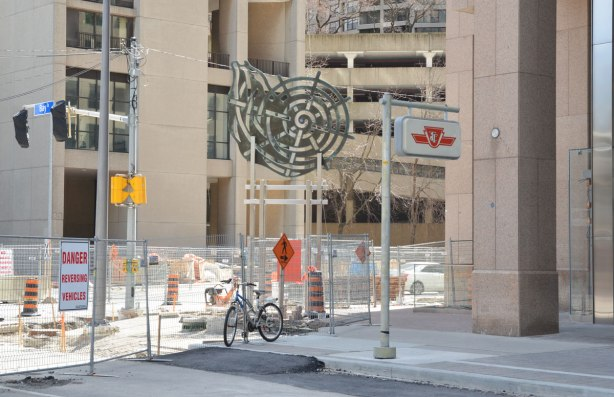 Public art installation called 'Nautilius' by Judith Scwarz which is a two dimensional cut out piece of metal of a snail-like spiral, mounted about ten to 12 feet off the ground on square sided metal poles. It is an a sidewalk amongst a lot of other things, TTC sign, condos, construction fences, a parked bike, construction signs etc.