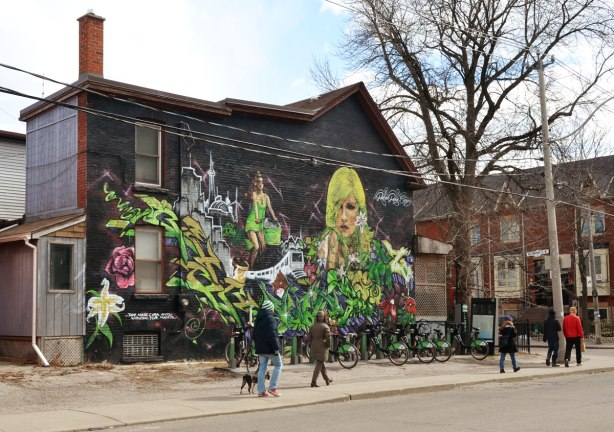 The side of a brick house is covered with a mural showing a woman's upper body and she has yellow and green hair.  Also, there is a woman on a bike with a Toronto scene behind her including the CN Tower and a TTC subway car below her.   There are lots of flowers including red roses and white lilies in the picture. The mural is signed by Robert  (Reber?) Rian Cruz.